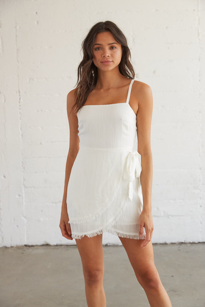 This simple white dress features a layered wrap design and an adjustable side tie detail.