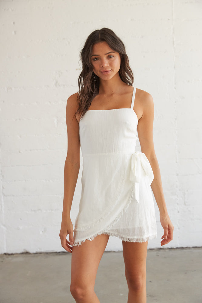 White wrap dress with a side tie detail and a frayed hem.