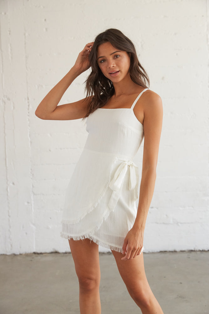 White mini dress with a side tie detail, a frayed hem, and a straight across neckline.