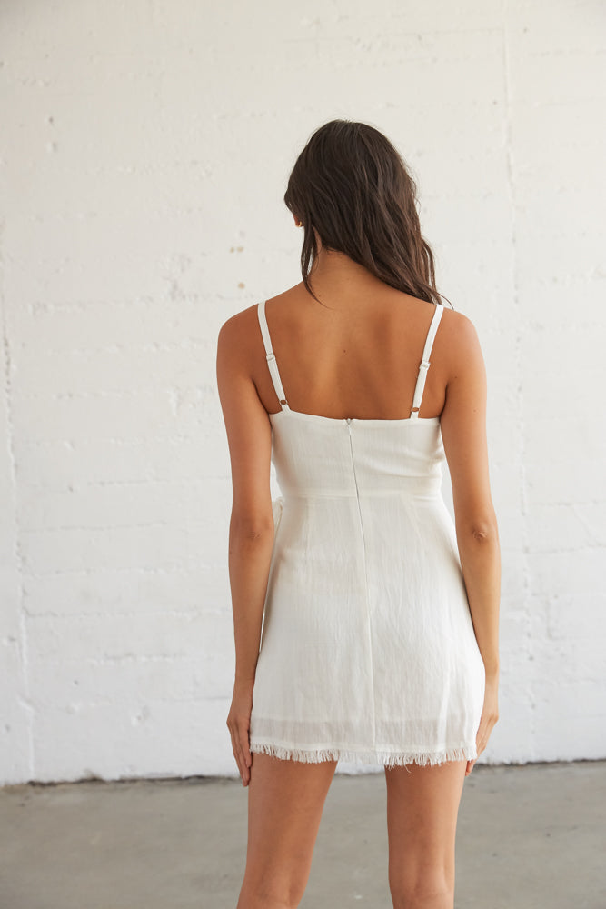The back of this white dress is complete with adjustable spaghetti straps and a back zipper closure .