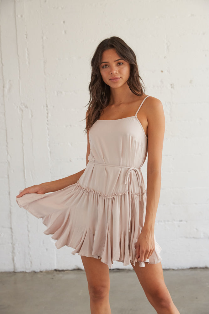 Light pink flowy dress with a straight across neckline and a tie at the waist.