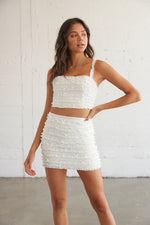 This adorable white two piece set is complete with ruffle detailing throughout.