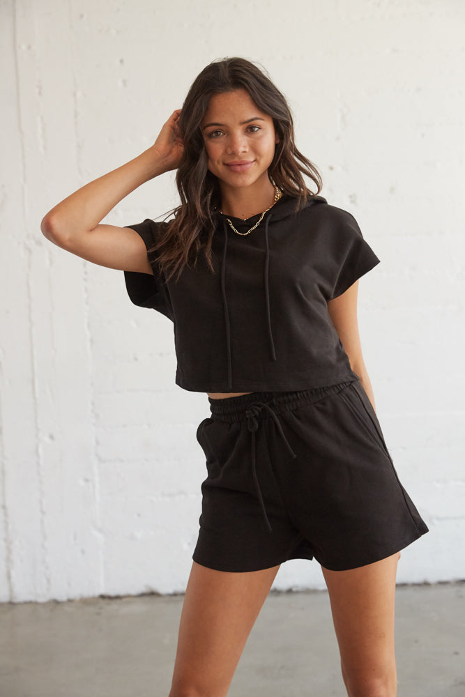 Black cropped hoodie with matching high rise shorts.