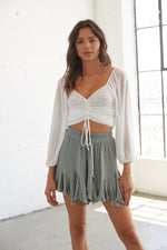 Sage green flowy shorts with ruffle detailing.