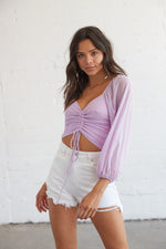 Lavender mesh top with flowy sleeves and a front tie detail.