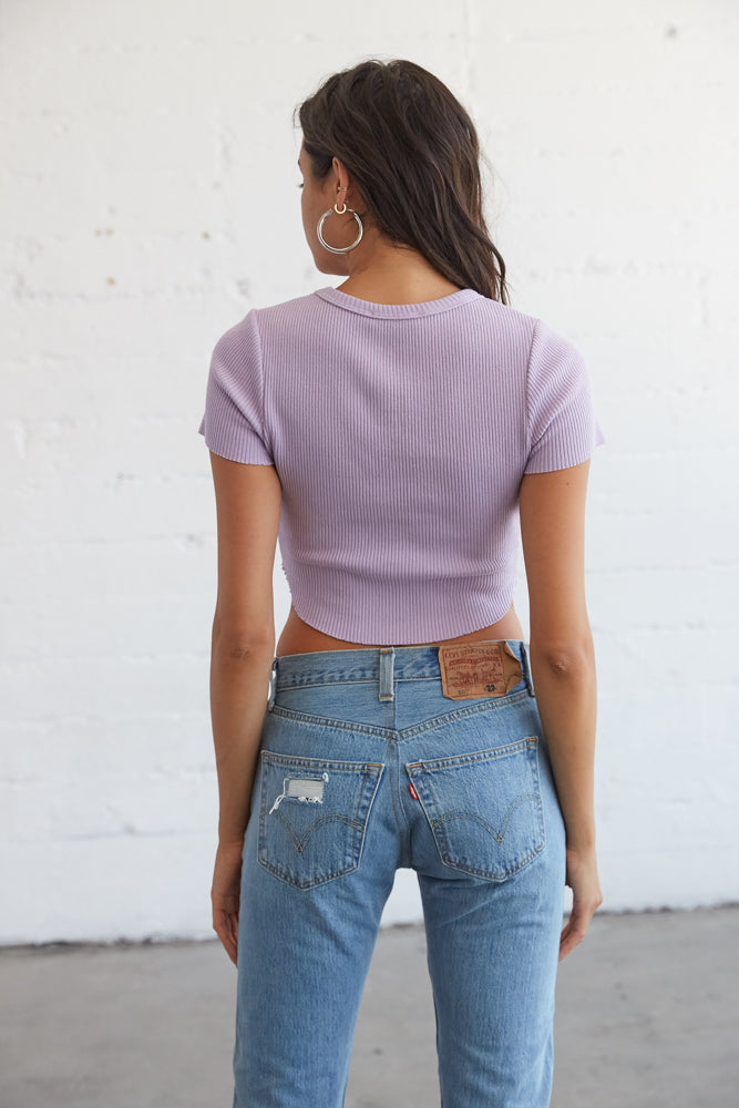 The back of this ribbed crop top is simple with a curved raw hem and short sleeves.