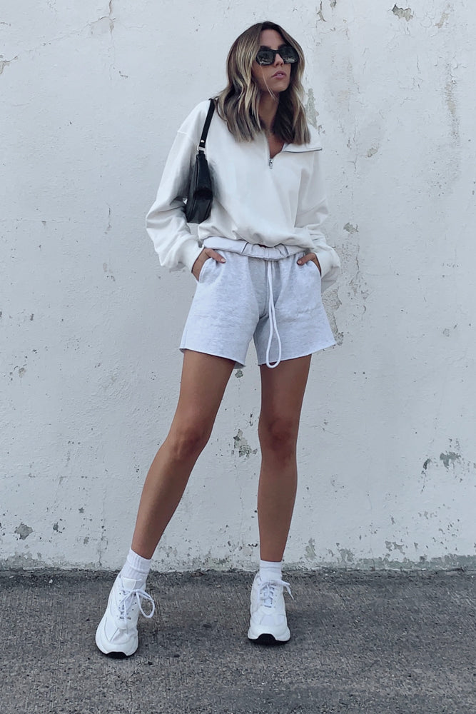 White pullover sweatshirt with oversized silhouette and half zip detail.