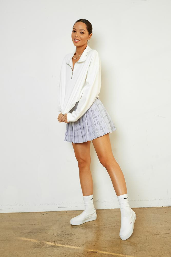 This white sweater is paired with a blue plaid skirt.