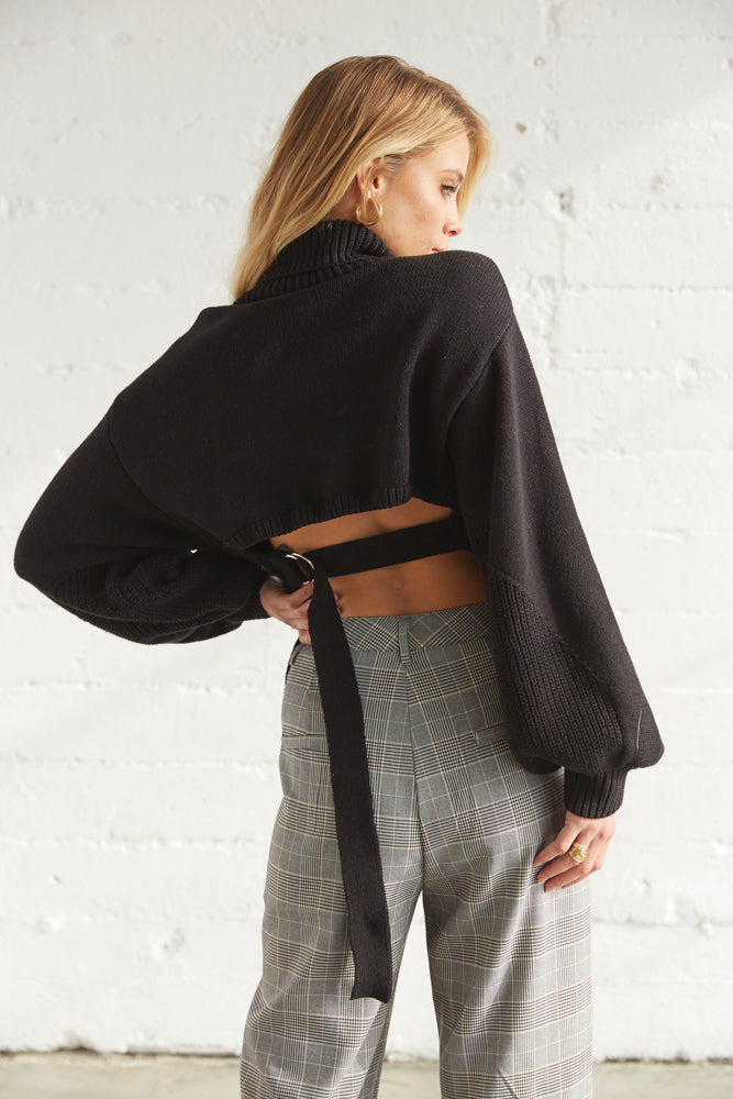 The back of this sweater is open with a belted design.