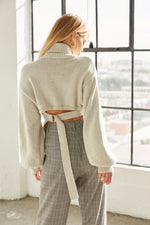 The back of this sweater has an adjustable belt tie detail.