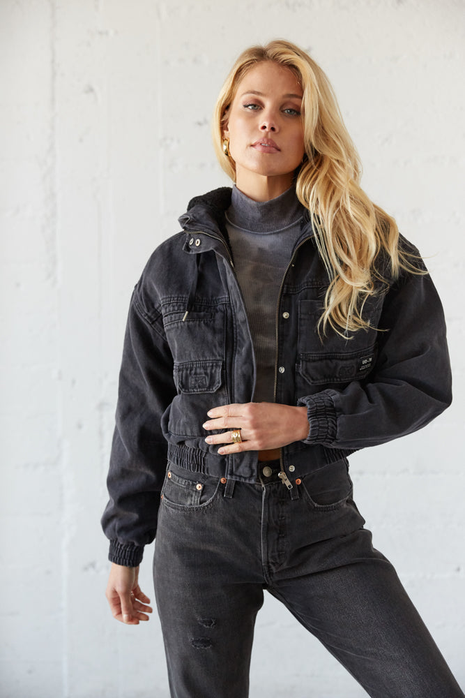 Cropped jacket with zipper and snap closures in the front.