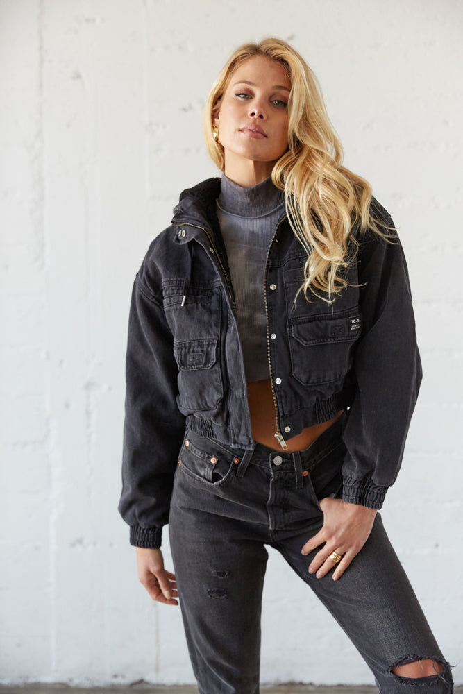 Black cropped cargo jacket with 5 pockets and long sleeves.