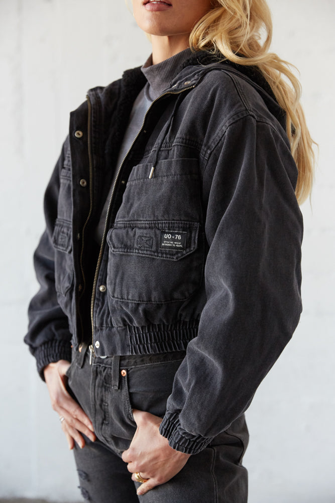This cropped denim jacket has long sleeves and an attached hood.