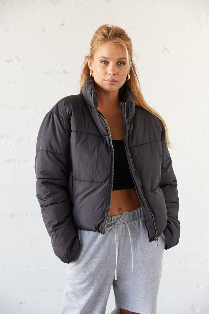 Black puffer jacket with zip up front.
