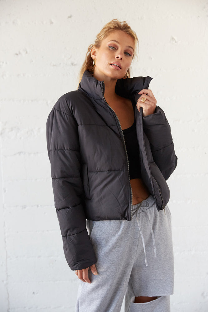 Black puffer jacket with side pockets.