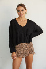 Slouchy black sweater with long sleeves.