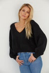 Black boxy cropped sweater with long sleeves.