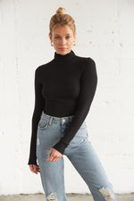 Black mock neck top with long sleeves.