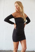 Details of the ruched design on this black mini dress.