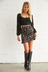 Black satin floral mini skirt.