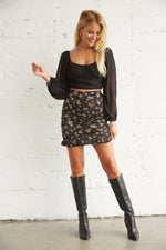Black mini skirt with ruffle trim.