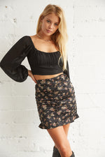 Black satin ruched mini skirt.