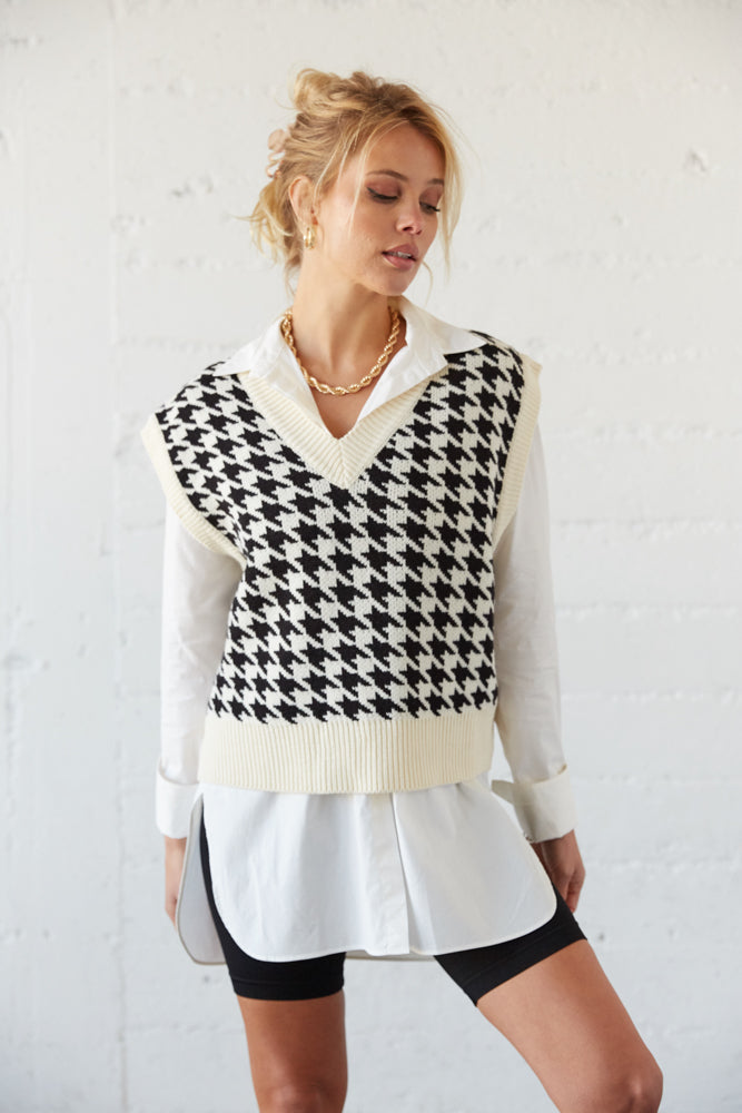 Houndstooth sweater vest with V neckline.