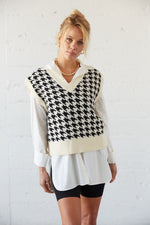 Black and white houndstooth vest with white shirt underneath.
