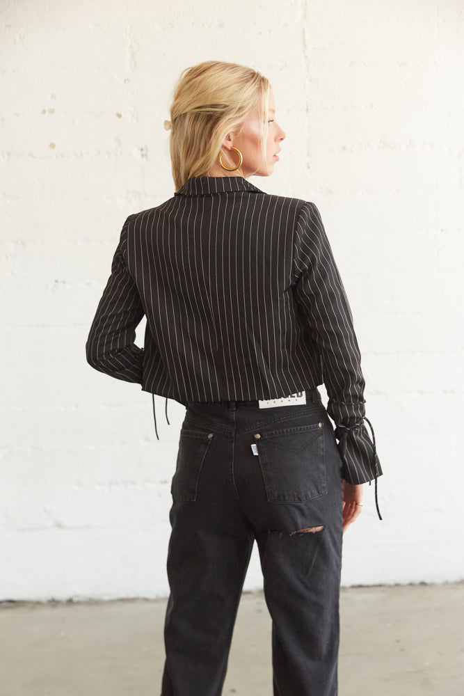The back of this cropped blazer has a collar and a pinstriped design.