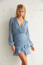Blue ruffle dress with ruched detailing throughout.