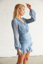 The side of this dress has ruched detailing and long sheer sleeves.