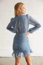 The back of this dress has ruched detailing and a keyhole cutout with button closures.
