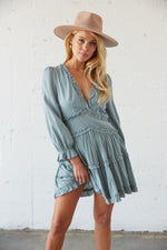 Blue ruffled mini dress with long sleeves.