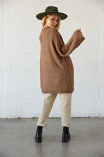 The back of this sweater has a loose knit design and a ribbed hem.