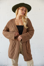 Brown oversized sweater with cable knit design.