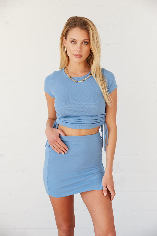 Blue cinched crop top with short sleeves.