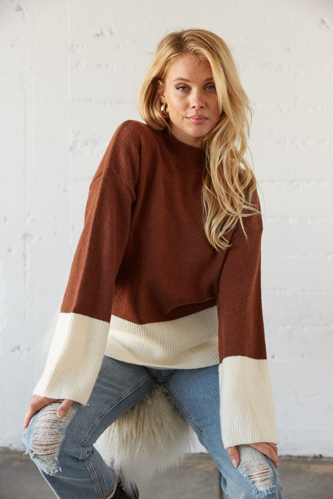 Chocolate brown oversized sweater with white horizontal stripe.