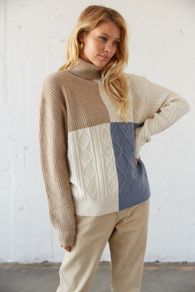 Colorblock turtleneck sweater with cable knit detailing.