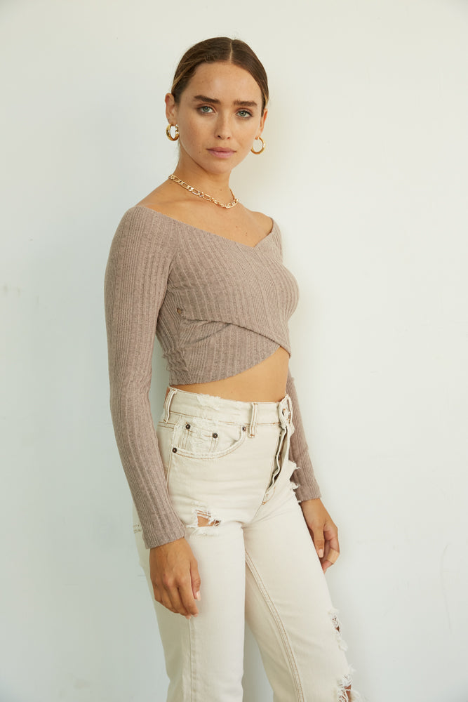 This crop top has long sleeves and a v neckline.
