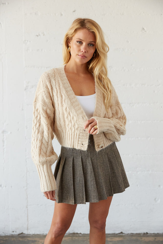 Cropped knit cardigan with front button closures.