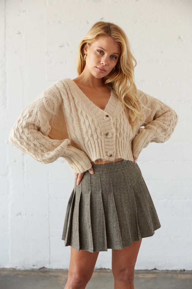 Pleated plaid tennis skirt with cropped chunky cardigan.