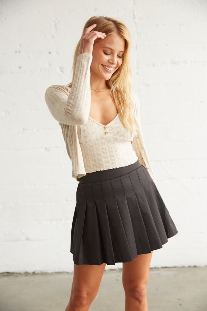 Black pleated mini skirt with tan sweater.