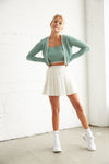White mini tennis skirt with green sweater.