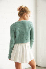 The back of this sweater is cropped with cable knit detailing.