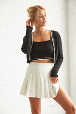 Pleated white skirt with black crop sweater and matching cardigan.