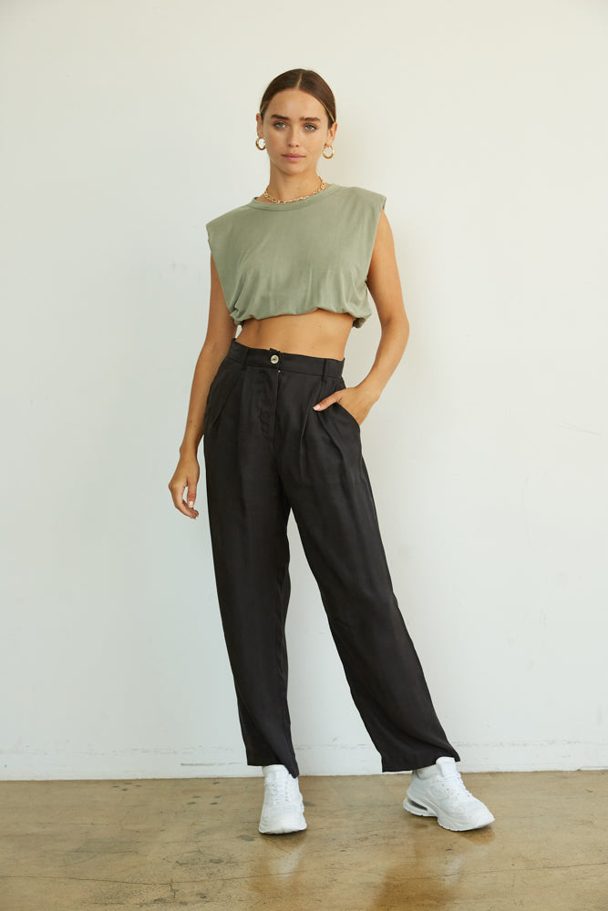 Black loose fit trousers with button closure.