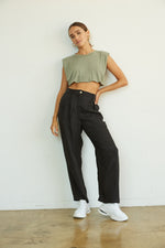 Black trousers with cropped muscle tee.