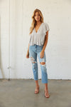 Flutter sleeve top with destroyed straight leg jeans.