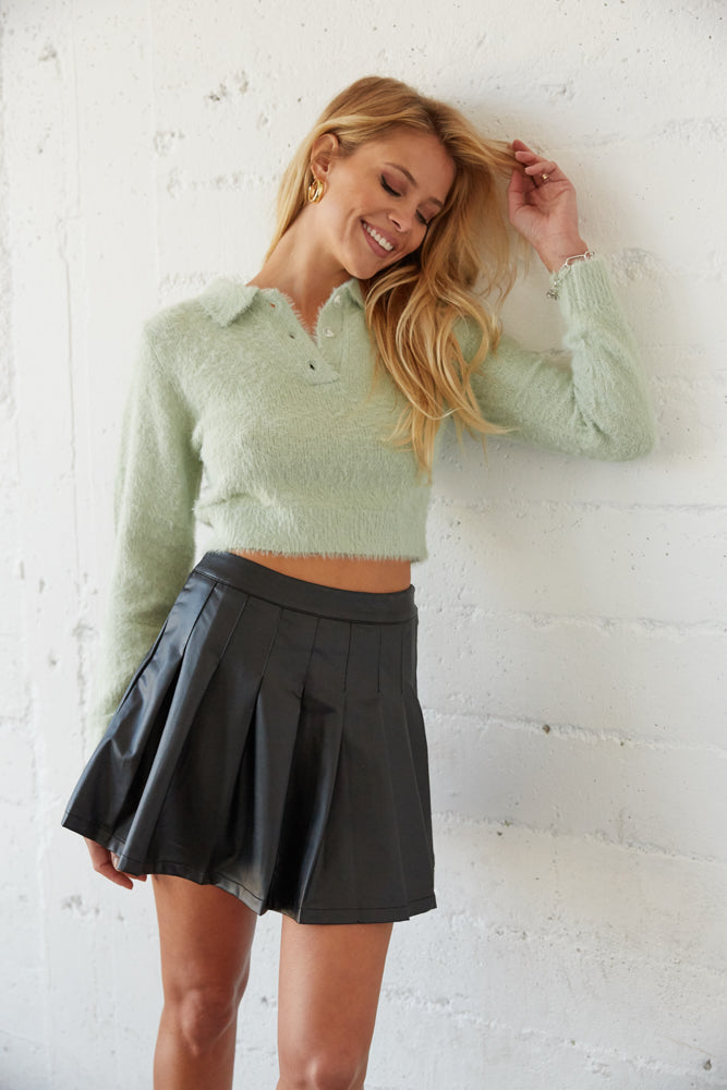 Green fuzzy sweater top with collared neckline. .