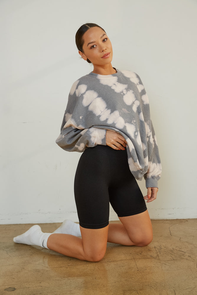 Black biker shorts with tie dye sweatshirt.
